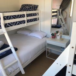 Pair of bunk beds with mirror and bedside table.
