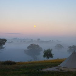Sunrise with fog and bell tent