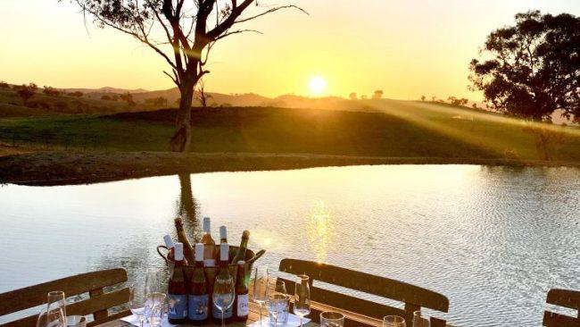 sunset at Glenayr Farm over hills, dam and table setting with wine